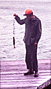 Tight photo of man holding up a fish