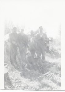 Group of guys in grass with bright light behind them (Cropped)