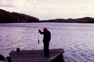 Wide photo of lake and man holding up a fish
