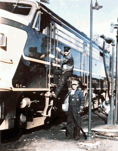 Faded photo of two guys boarding a train engine