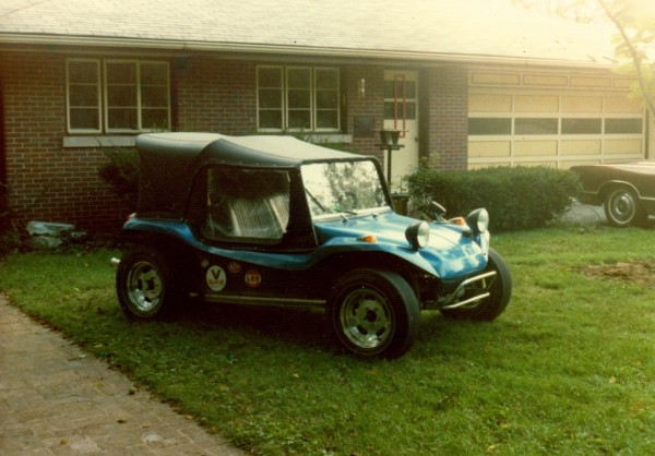 Blue dune buggy in front yard grass