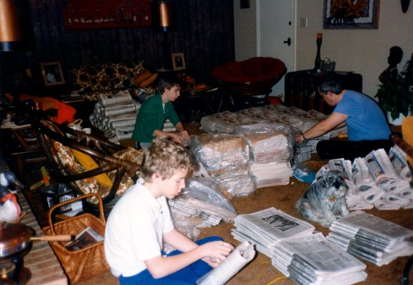 Three guys sitting on carpet putting Sunday newspapers together for paper route