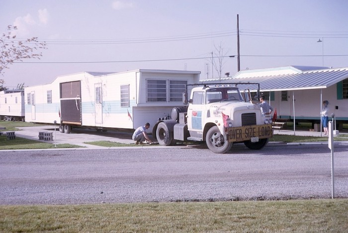 Mobile home being moved into place by old semi truck.