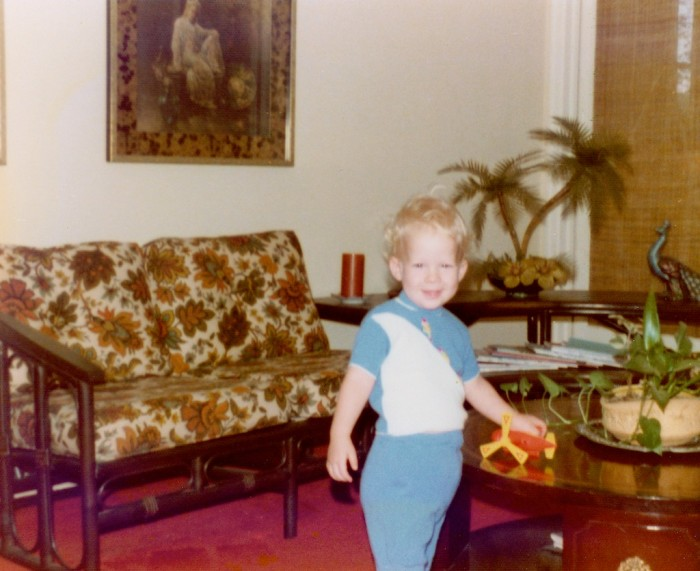 little boy standing in front of a rattan-like couch clearly made in the 1960's to 1970's