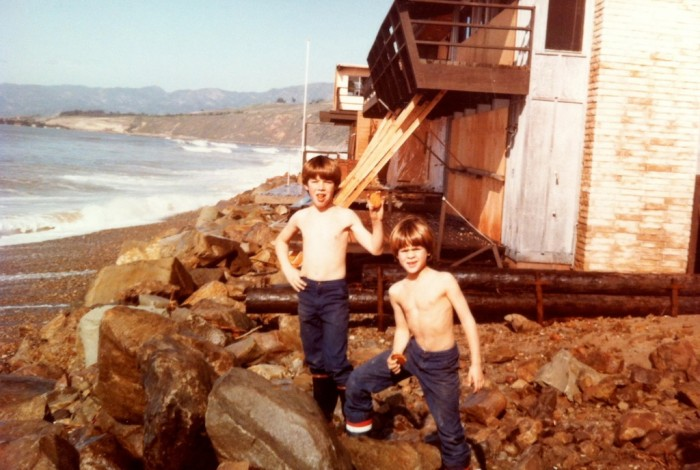 two boys in front of beach house damaged by ocean wave