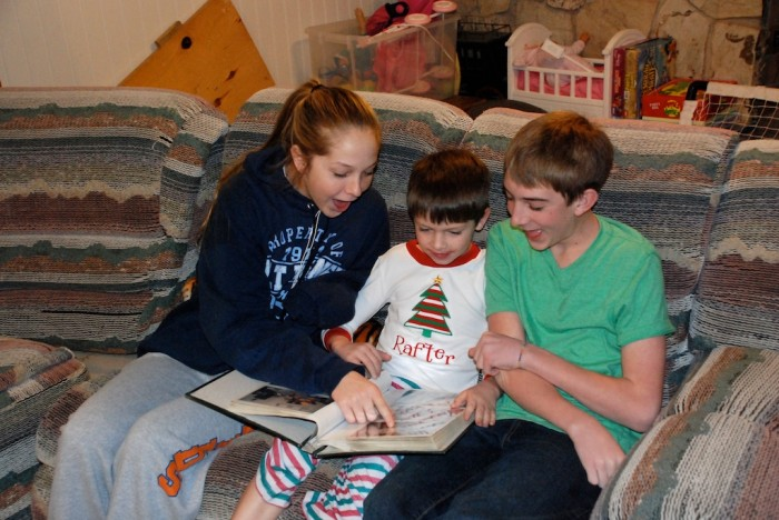 children looking at family photo albums on couch