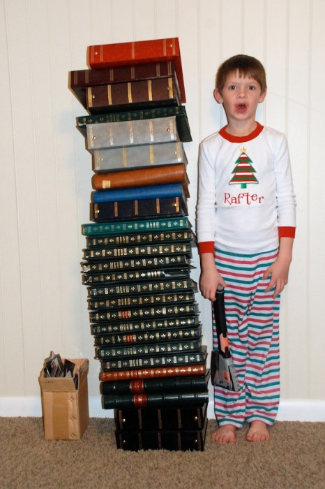 boy standing next to a stack of photo albums that need to be digitally scanned