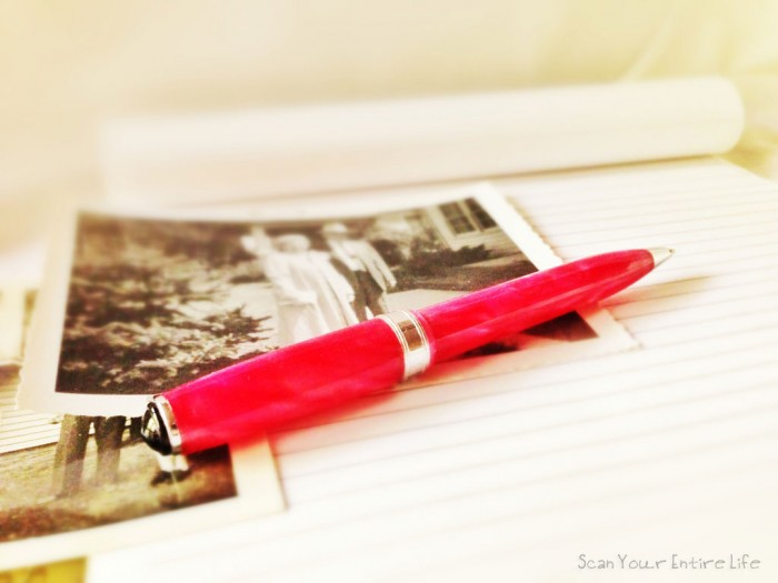 How to Write an Autobiography - Nice fancy pink pen resting on notepad and a couple paper prints