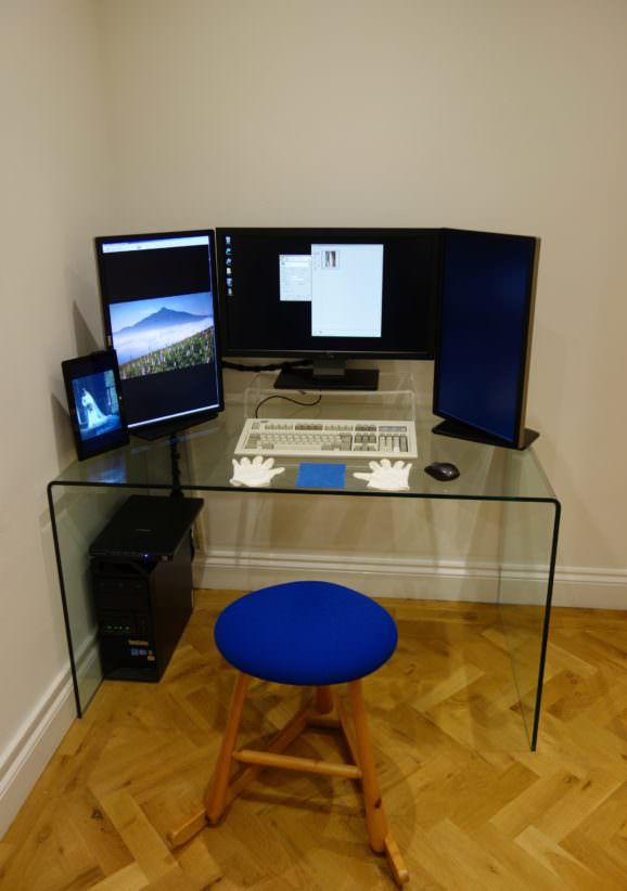 Scanning workstation on glass table - three monitors, white gloves and stool