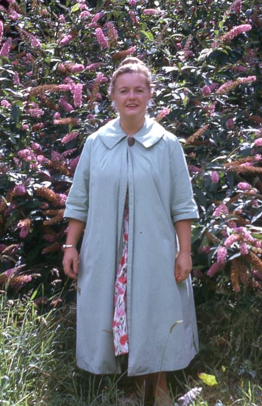 Lady in blue long coat standing in front of blossoming tree