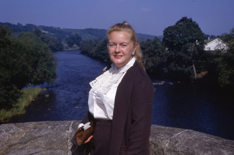 Well-dressed Lady standing next to ledge overlooking river