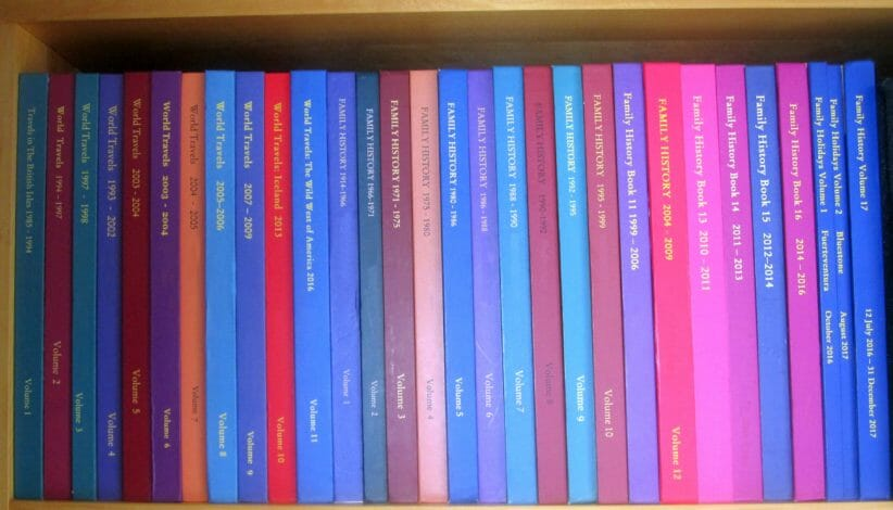 colorful labeled photo books lined up on a shelf