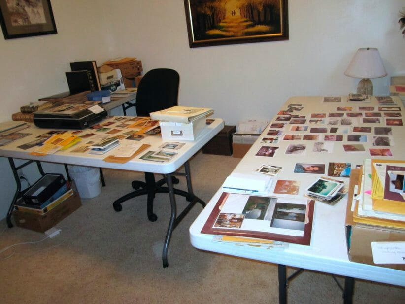 room with 2 folding tables set up with stacks of photos on top