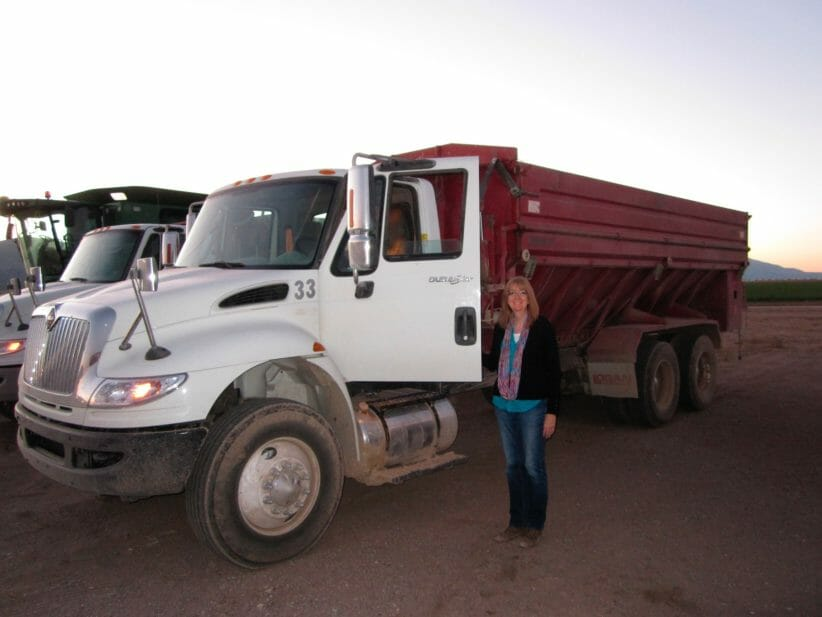 woman standing next to open cab of large truck